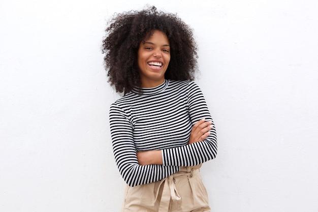 Mulher negra sorridente na camisa listrada com os braços cruzados