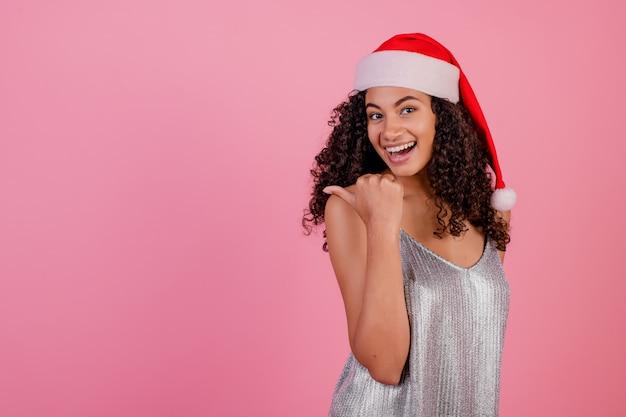 Mulher negra sorridente usando chapéu de papai noel e vestido festivo