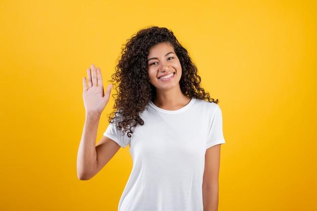 Mulher negra sorrindo acenando olá com a mão isolada sobre amarelo