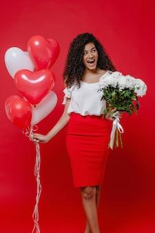 Mulher negra, sorrindo com balões em forma de coração e buquê de flores brancas na parede vermelha