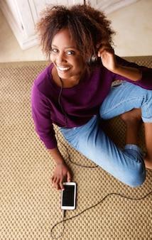 Mulher negra, sorrindo com smart phone e fones de ouvido