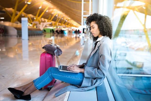 Mulher negra, trabalhando com o laptop no aeroporto esperando na janela
