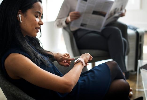 Mulher negra usando fones de ouvido usando um smartwatch