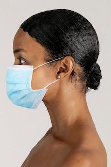 Mulher negra usando máscara cirúrgica em uma foto de perfil