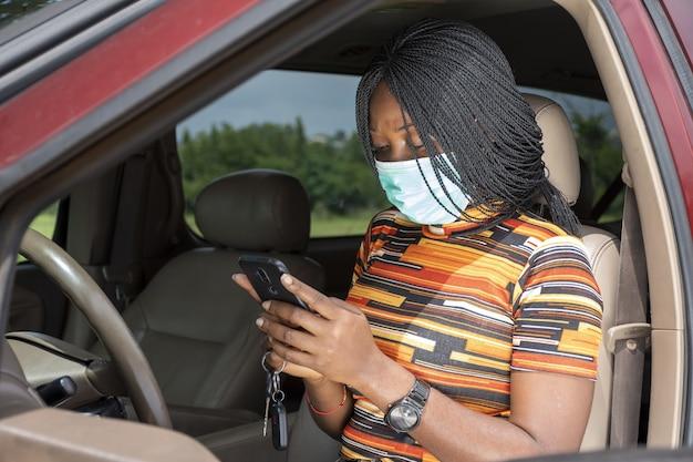 Mulher negra usando seu telefone enquanto está sentada em um carro, usando uma máscara facial - o novo conceito normal