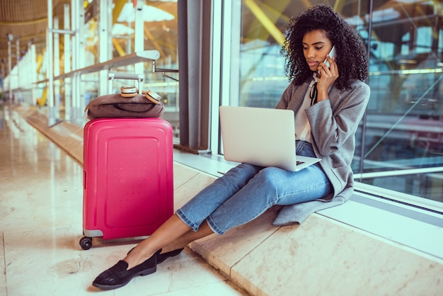 Mulher negra, usando telefone celular e laptop no aeroporto, sentado à janela