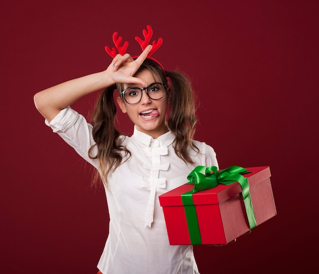 Mulher nerd com presente de natal mostrando sinal de perdedor