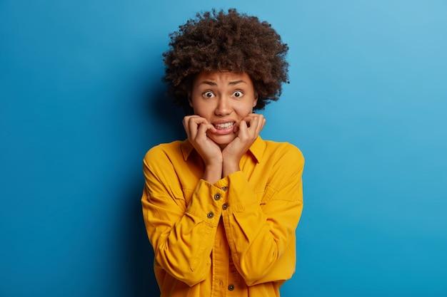 Mulher nervosa assustada cerra os dentes, entrando em pânico por estar em perigo, fica envergonhada, veste camisa amarela, isolada sobre fundo azul.