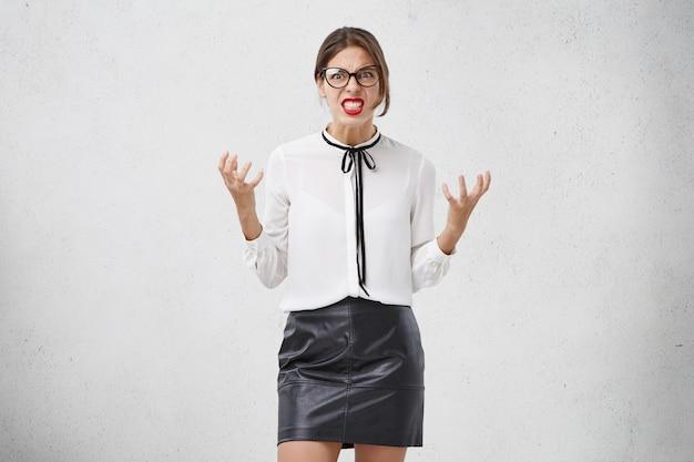 Mulher nervosa e indignada com dentes entrelaçados, gestos com as mãos com raiva,