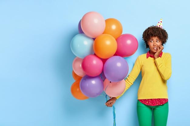 Mulher nervosa e perplexa segurando balões multicoloridos enquanto posa com um suéter amarelo