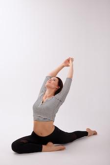 Mulher no asana em um fundo branco no estúdio. aulas de ioga. caneleiras desportivas pretas e top. dia internacional da ioga