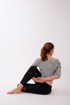 Mulher no asana marichiasana d em um fundo branco isolado. dia internacional da ioga