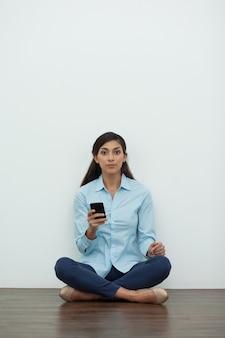 Mulher no assoalho no pose de lotus com smartphone