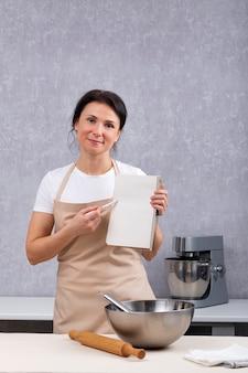 Mulher no avental da cozinha na cozinha com um livro de receitas nas mãos explica a receita. quadro vertical.