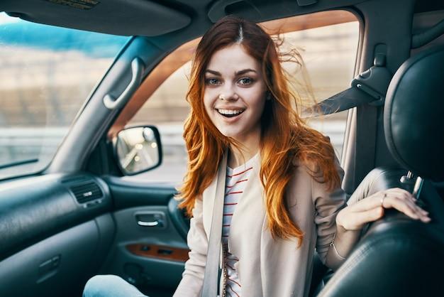 Mulher no banco da frente do carro, voltada para trás e janela design salão de viagens companheiro de viagens turismo