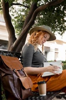 Mulher no banco escrevendo no diário