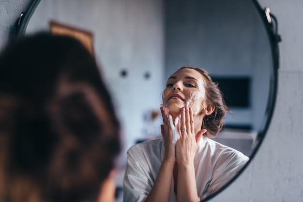 Mulher no banheiro lavando o rosto com espuma