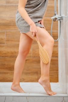 Mulher no banheiro realiza cuidados com a pele das pernas das coxas para remover células mortas da pele. conceito de cuidados com o corpo.