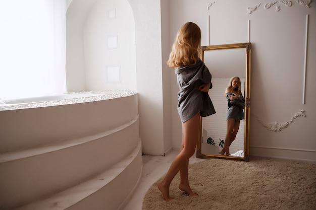 Mulher no banheiro se olha no espelho