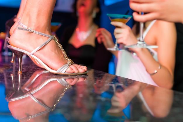 Mulher no bar ou clube está dançando em cima da mesa