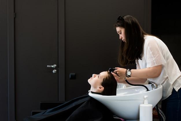 Mulher no cabeleireiro, lavando o cabelo e enxaguando, sentindo-se visivelmente bem