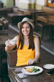 Mulher no café da rua ao ar livre, sentada à mesa, com um chapéu amarelo de roupas com uma xícara de cappuccino, bolo, relaxando no restaurante durante o tempo livre