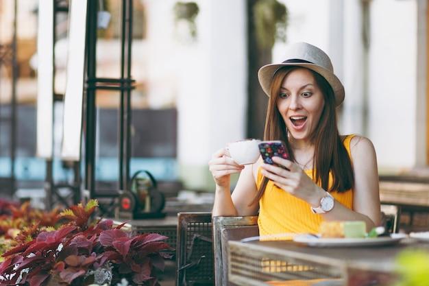 Mulher no café da rua ao ar livre, sentada à mesa com um chapéu com uma xícara de bolo de cappuccino, usando o telefone celular, relaxando no restaurante no tempo livre