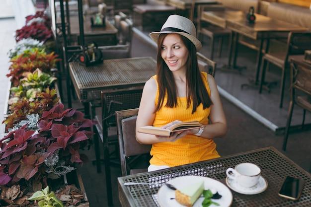 Mulher no café da rua ao ar livre, sentada à mesa com um chapéu, lendo um livro com uma xícara de cappuccino, bolo, relaxando no restaurante durante o tempo livre