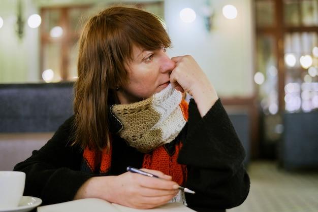 Mulher no café escreve no diário, jornal de bala.