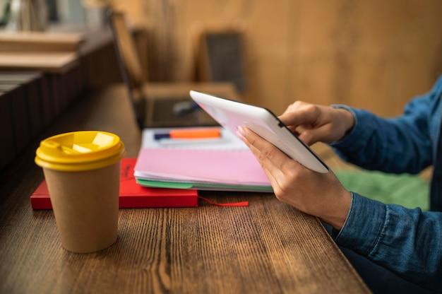 Mulher no café esperando os amigos chegarem para fazer o dever de casa