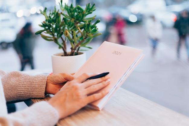 Mulher no café, perto da parede de vidro, segurando o bloco de notas do caderno de papel, sinal 2021