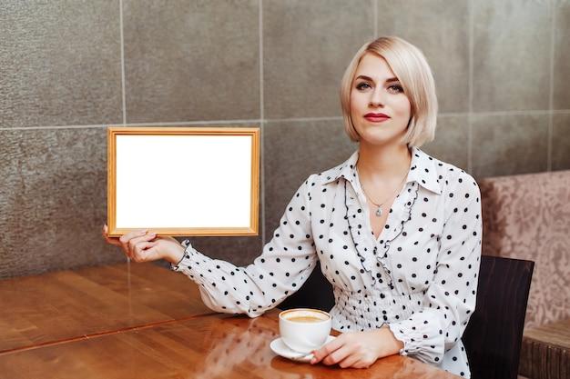 Mulher no café segurando a moldura de madeira