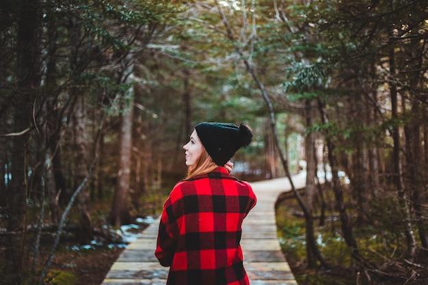 Mulher no caminho entre árvores