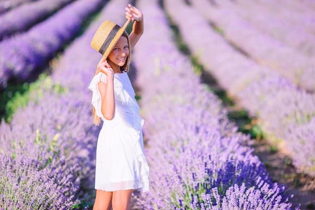 Mulher no campo de flores de lavanda ao pôr do sol com vestido branco e chapéu