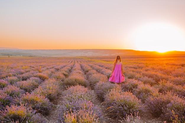 Mulher no campo de flores de lavanda ao pôr do sol em vestido e chapéu branco