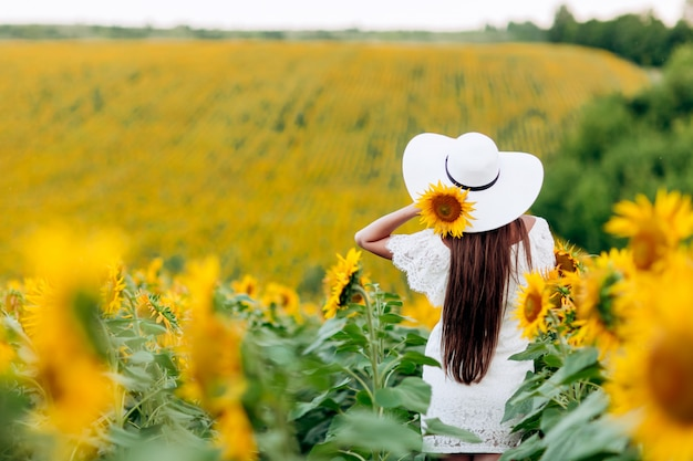 Mulher no campo de girassóis. uma garota feliz e bonita com um chapéu branco está de pé em um grande campo de girassóis. horário de verão. vista traseira. foco seletivo.