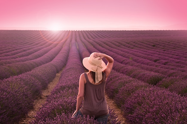 Mulher no campo de lavanda no pôr do sol rosa