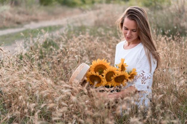 Mulher no campo segurando girassóis