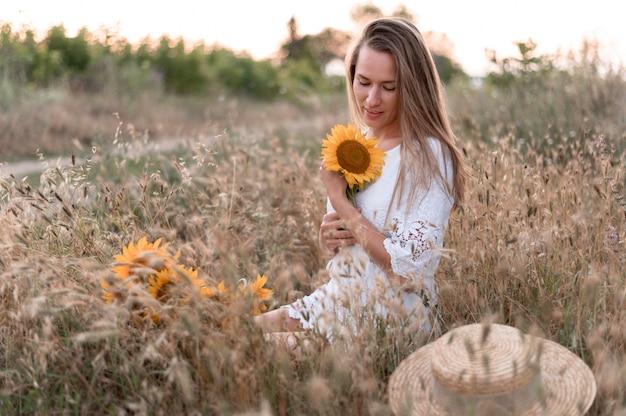 Mulher no campo segurando girassol