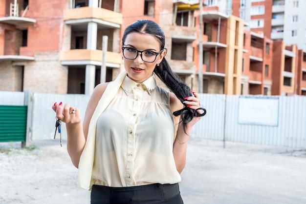 Mulher no canteiro de obras com as chaves do apartamento