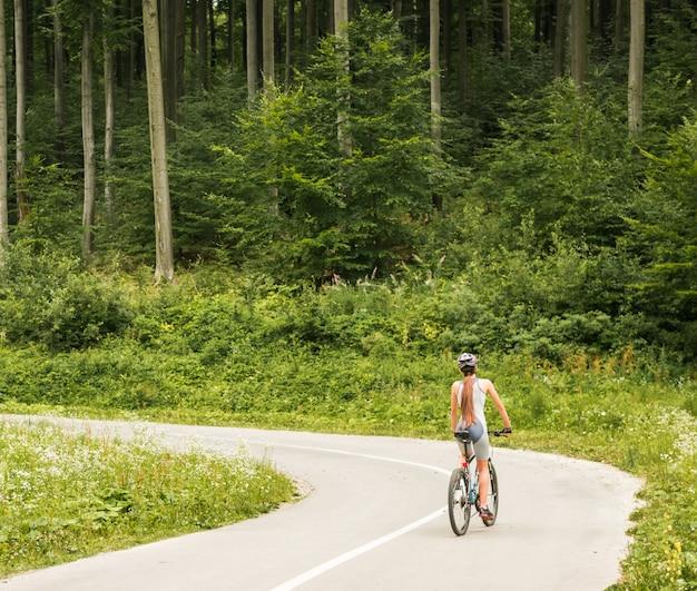 Mulher no capacete andando na bicicleta de montanha.