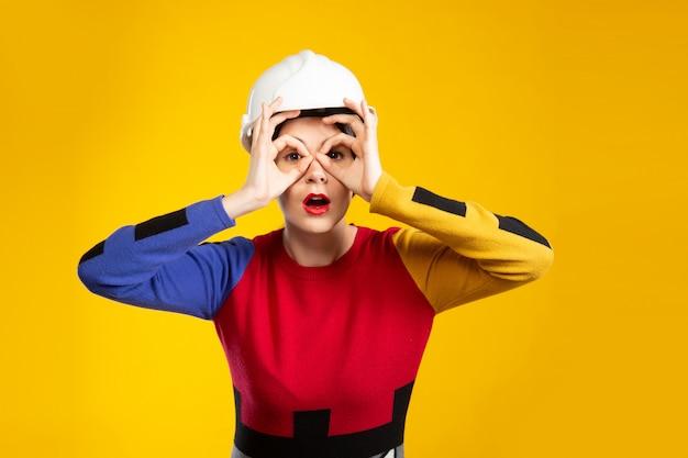 Mulher no capacete de construção mostra óculos com os dedos
