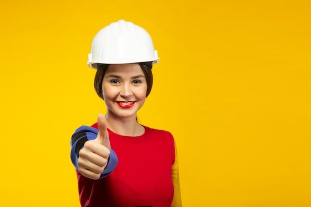 Mulher no capacete de construção mostra os polegares