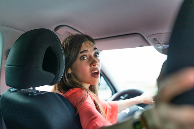 Mulher no carro olhando os passageiros no banco de trás