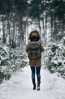 Mulher no casaco de inverno quente com capuz de pele e mochila grande viagem na floresta de inverno nevado
