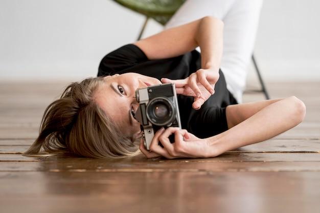 Mulher no chão tirando uma foto