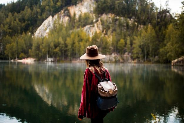 Mulher no chapéu e na camisa vermelha perto do lago no montanhas.