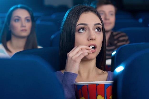 Mulher no cinema. mulher jovem e atraente comendo pipoca e assistindo filme enquanto está sentado no cinema
