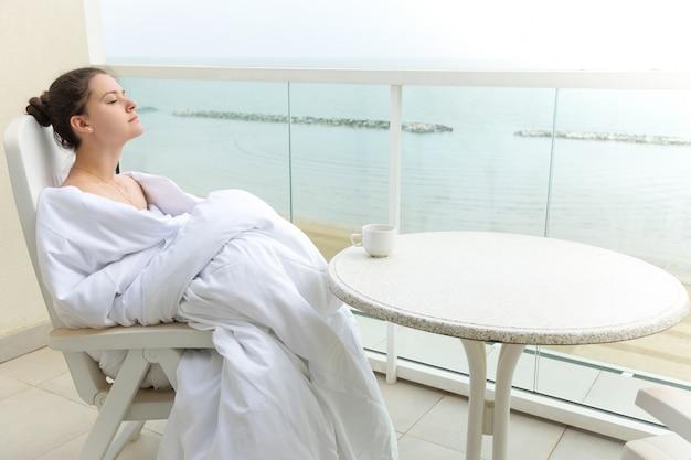 Mulher no cobertor branco, bebendo café no terraço em casa