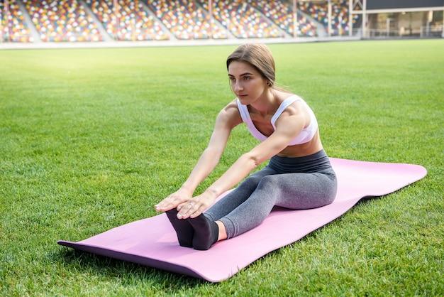 Mulher no colchonete fazendo exercícios matinais na grama verde